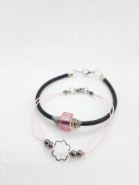 roze en zwart armbandje, een met een resinkraal de ander met een zilverkleurig tussenzetsel.